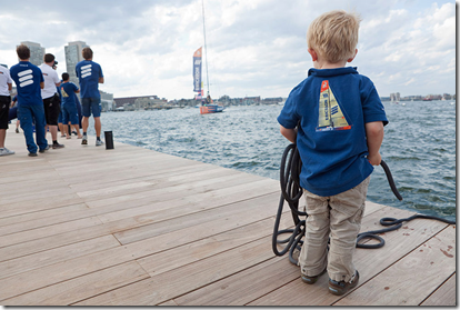 Navigator Jules Salters' (UK) son Fred is eager to tie daddy's boat to the dock as he arrives in Boston harbor. (© Oskar Kihlborg)