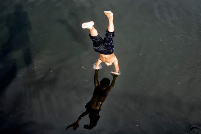 A boy dives into the Dambovita river to cool off in Bucharest, Romania, Wednesday, Aug. 11, 2010. (AP Photo)