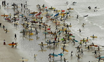 South African surfers take to the water in an attempt to break the Guinness World Record for the highest number of riders on a single wave at Muizenberg in Cape Town, September 26, 2010. (REUTERS/Mike Hutchings)
